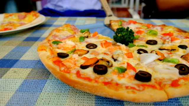 Pizza and sausage fried on the table, moving from left to right. video