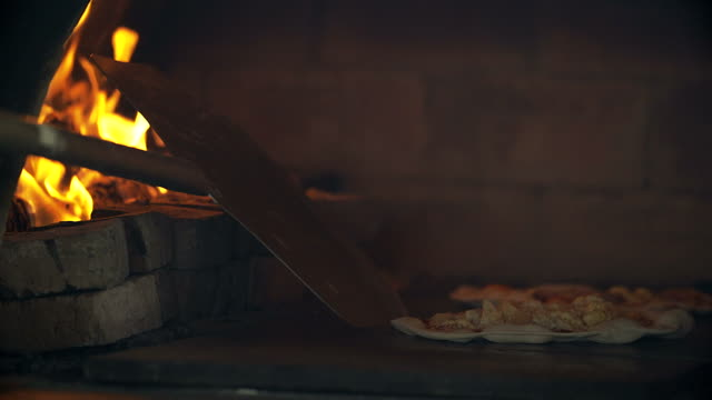 4K: Pizza baking in brick pizza oven video