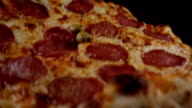Pizza salami falls on a black surface video