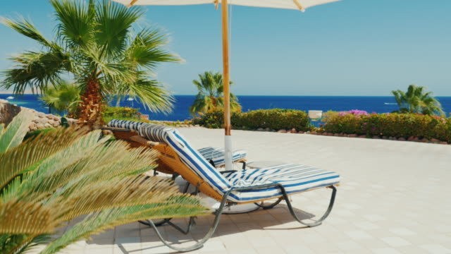 A place of paradise rest. Beach umbrella and blue sea on a sunny day. Crane shot video