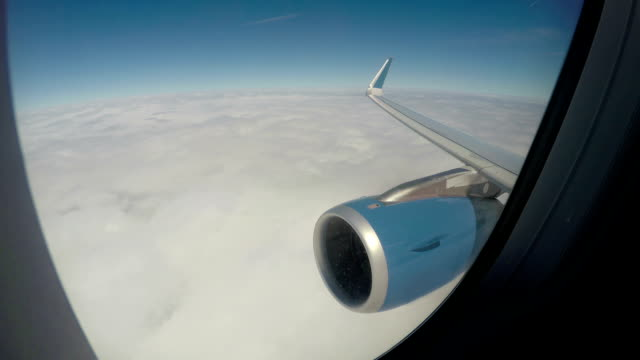 Plane flying above thick white clouds in tranquil blue sky, vacation travel video