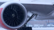 Plane parked at the airport. Ready to fly. The turbine close-up. In winter snow storm. video