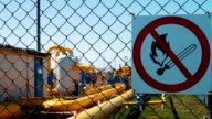 Plant for processing natural gas. Warning of fire hazard on the fence. Transportation and processing of natural gas. Pipeline with shut-off valves. Gas and oil industry video