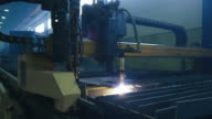 CNC plasma cutter is cutting out metal objects in a heavy industry factory. video