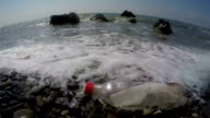 Plastic bottle with message brought to shore by sea waves slow motion video