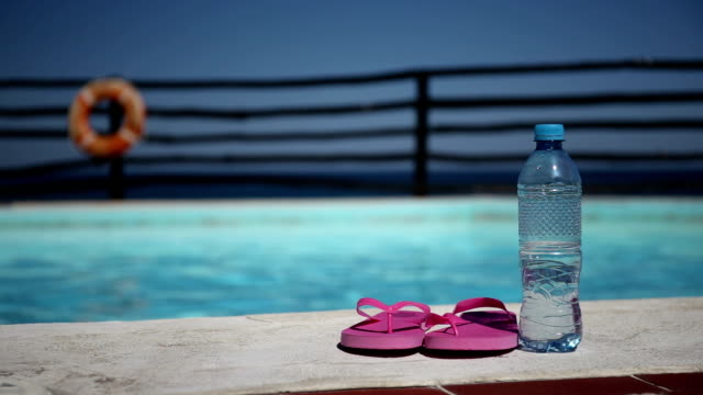 Plastic bottle with pure water and slippers near swimming pool video