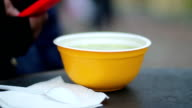 Plastic bowl of hot soup served outdoors for menial workers, video