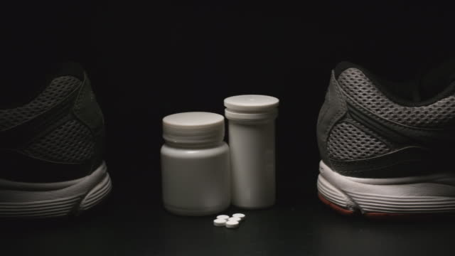 DOPING: Plastic containers, pills and sport shoes (back) - Dolly shot video