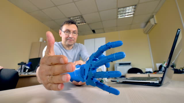 A plastic robotic arm prototype is tested in a lab. video