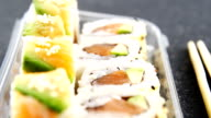 Plastic tray of various sushi rolls with salmon video