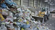 CS plastic waste being piled up by a backhoe loader video