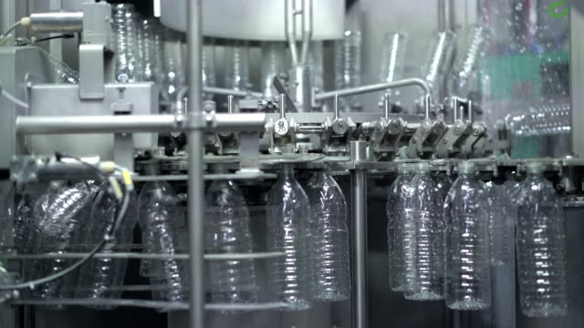 Plastic water bottles on conveyor and water bottling machine industry. video