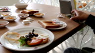 Play smartphone while eating breakfast. video