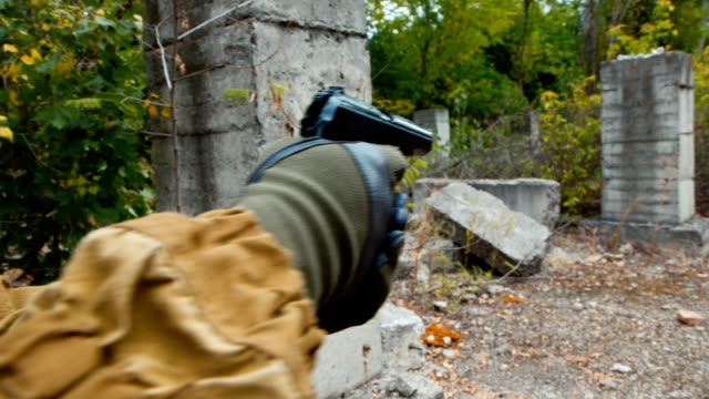 A player in airsoft with a pneumatic gun searches for the enemy, takes aim. Back view video