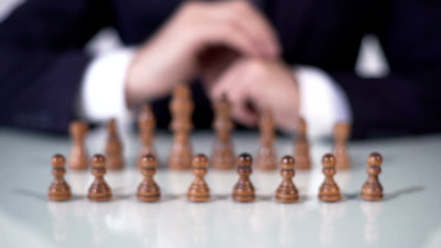 Player sacrificing pawn in chess game, startup company entering large market video