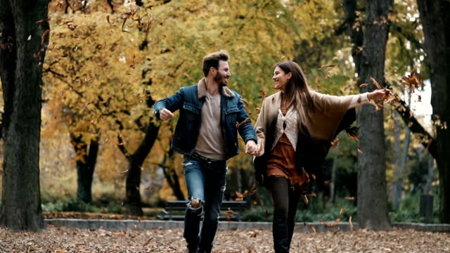Playful couple throwing autumn leaves in the air while running in nature. Slow motion. video