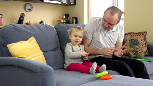 playful father have fun with baby girl on sofa at home. Man tickle toddler girl video