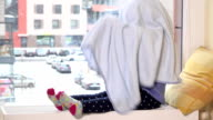 Playful girl with towel on her hair sitting on radiator near window. Snowstorm video