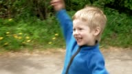 Playful little boy runs on game laughs and smiles video