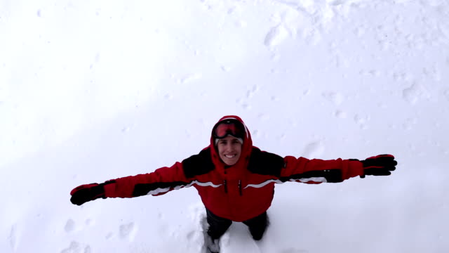 Playful man makes snow angel video
