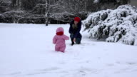 Playful mother with dummy attract baby child to walk on snow in winter. FullHD video