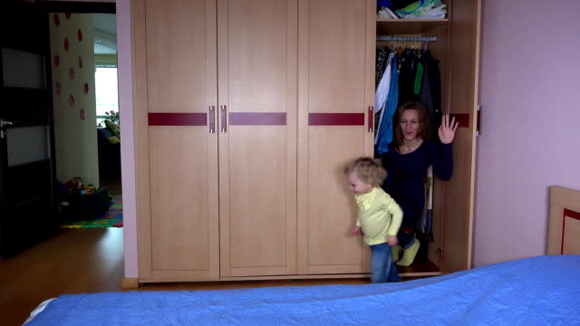 Playful woman and her daughter girl get out from closet and run away. video