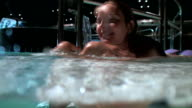 Playful woman enjoying in a wellness pool; underwater camera video