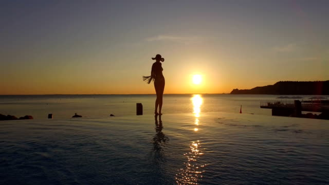 AERIAL: Playful woman standing on edge of infinity pool admiring magical sunset video