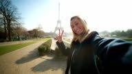 Playful woman taking selfie at Eiffel tower-Peace sign video