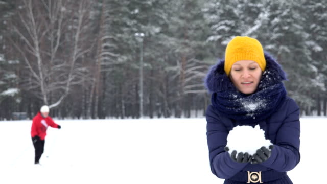 Playful woman with yellow hat blow fluffy snow and skier man on background. video