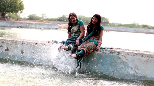 Playful woman's legs splashing water video