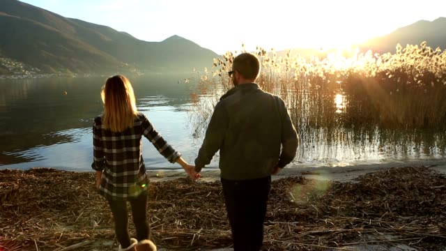 Playful young couple by the lake holding hands video