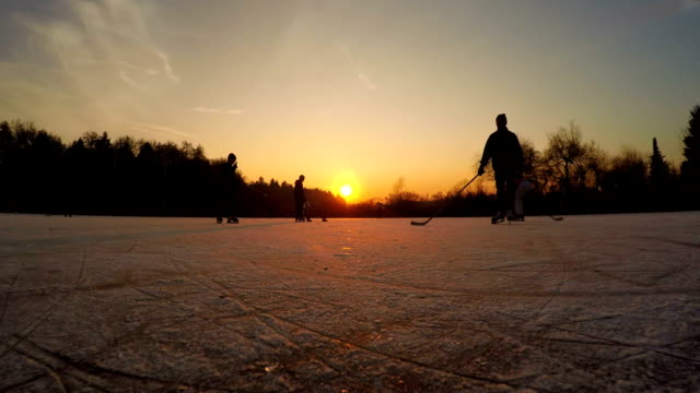 FPV LOW ANGLE: Playful young people iceskating and on ice pond at golden sunset video