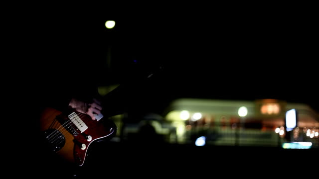 Playing guitar by the city road in night video