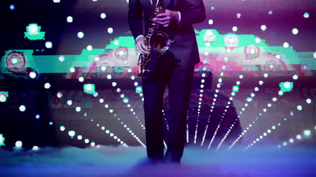 Playing saxophone in night club no face close up hands and legs only. Saxophonist playing his instrument at new years party with strobing and glitching vj screen projection background video