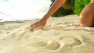 SLOW MOTION CLOSEUP: Playing with white sand at the beach video