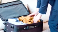 Pleasant businessman packing his suitcase video