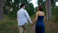 A pleasant man with a beard leads his beautiful wife or girl on a footpath in the woods video