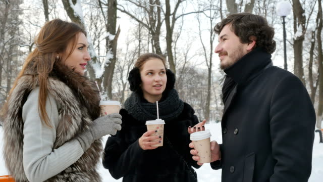 Pleasant people in the winter snow-covered park drinks a coffee video