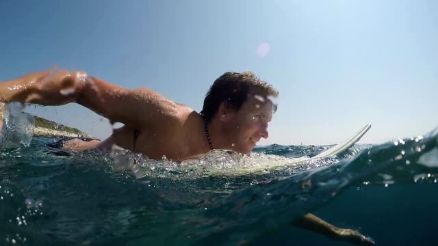 SLOW MOTION OVER-UNDER: Pleased surfer man paddling on surf in open water ocean video