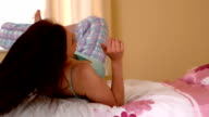 Pleased young woman rolling on her bed video
