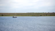 Pleasure boat cuts fluctuating surface of lake in day time video