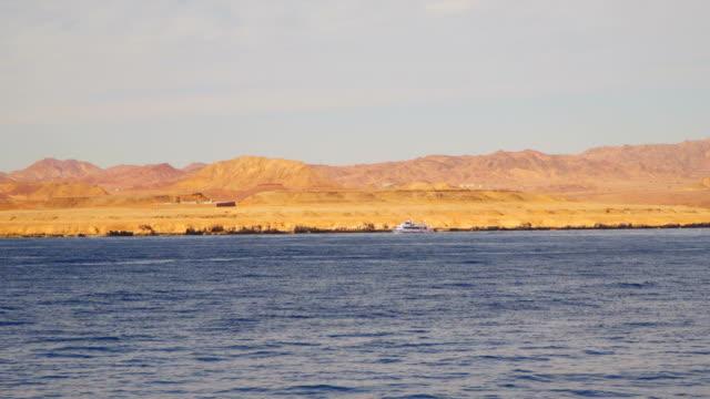 A pleasure boat sails near a deserted shore video