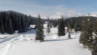 AERIAL: Plowed road leading to ski resort on plateau on dreamy white Christmas video