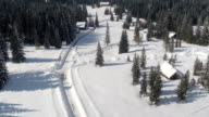 AERIAL: Plowed roads leading to houses and alpine lodge on plateau in wintertime video