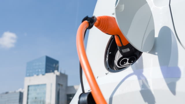 Plugging in electric car to charging station at an electric vehicle parking in downtown district video