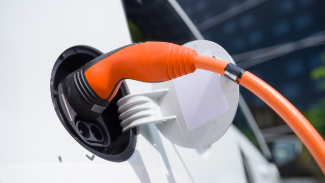 Plugging power cable into electric car to charge batteries in front of office video