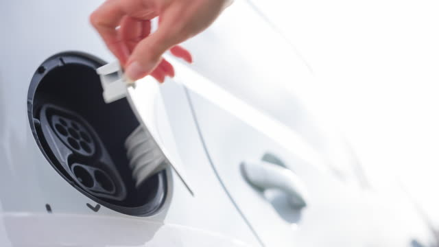 Plugging power cable to electric vehicle to recharge batteries video