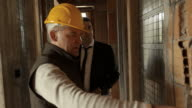 Plumber and architect talking, looking at blueprint in construction site video