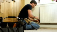 DOLLY HD - Plumber fixing Radiator in House video